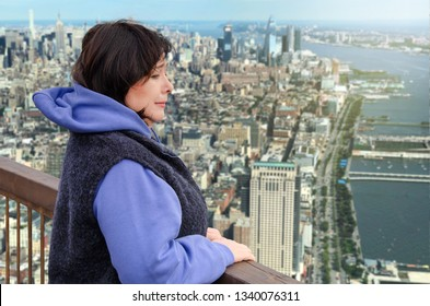 A woman is afraid of heights. She looks down on the panorama of the big city and she is scared. This mature woman tries not to show her fear. But it is clear how she suffers from acrophobia.