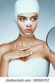 Woman after plastic surgery, looking in mirror. Photo of woman wrapped in medical bandages. Plastic Surgery concept
