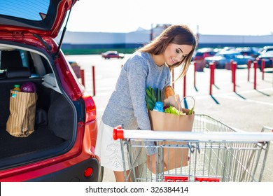 Woman after shopping in a mall or shopping center and driving home now with her car outdoor