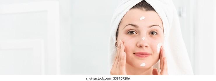 Woman after shower using moisturizing face cream