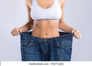 Woman after weight-loss is try her old jeans