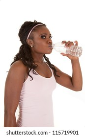 A woman after a workout drinking from a bottle of water.