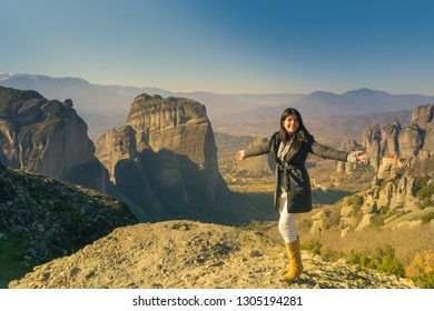 Woman against the Meteora in Greece. A beautiful place to travel.