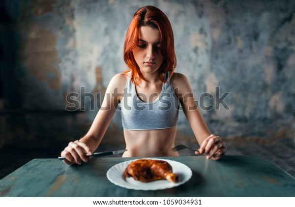 Woman against plate with food, absence of appetite