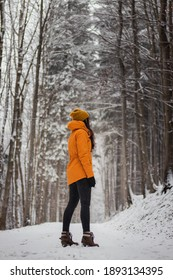 woman aged 20-24 standing in the middle of a snowy road and snowing around her. Portrait in antique white and Set Sail Champagne tone. Girl in a yellow winter jacket and black jeans.