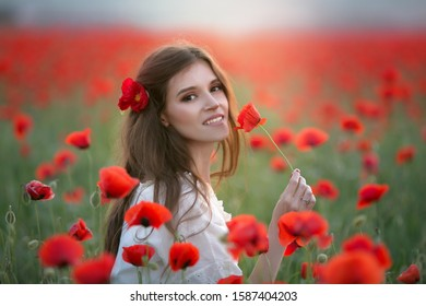 A woman in an agricultural field with a wreath on her head of red poppies.