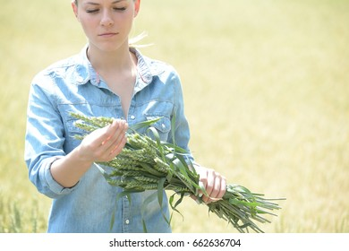 woman agriculture engineer standing in green wheat field with ears of wheat harvest for analysis