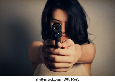 Woman aiming a gun,focus on the gun, grunge vintage style.