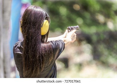 Woman aiming pistol at target out indoor firing range or shooting range.