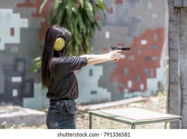 Woman aiming pistol at target out indoor firing range or shooting range.