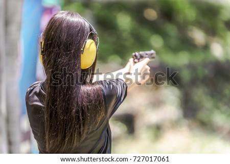 Woman aiming pistol at