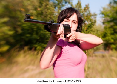 Woman aiming rifle in the sunny summer forest. Lensbaby effect
