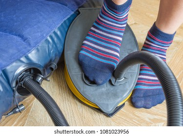 A woman with air foot pump pumps an inflatable mattress or air bed at home. Part of body, selective focus.