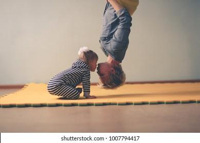 woman air yoga upside down kisses toddler, yellow hammock. Lifestyle and Toning