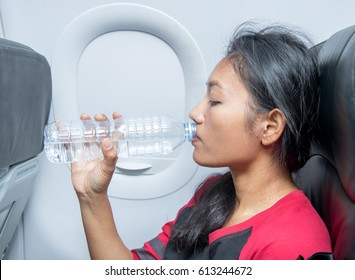 Woman in aircraft drinks water from a plastic bottle. A passenger plane flying in the refreshes drink from his bottle.