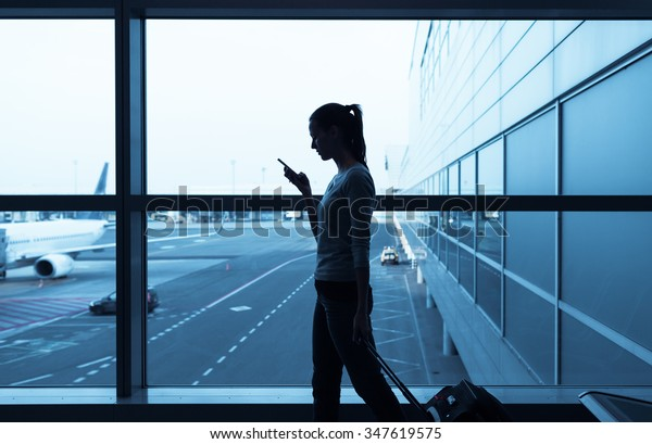 Woman at the airport using her cellphone.