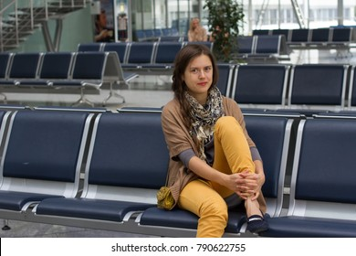 Woman in airport waiting on seat