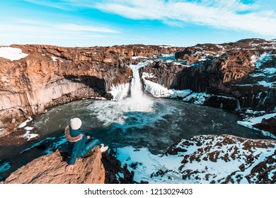 Woman at Aldeyjarfoss, Iceland. Tourist at famous waterfall in Iceland.