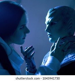Woman and an alien look at each other. Contact with other civilizations. Toning