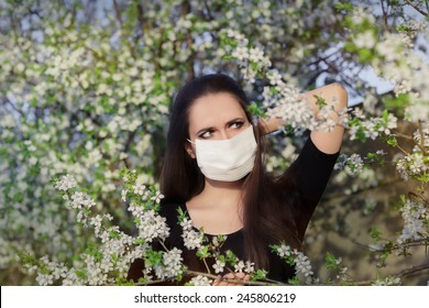 Woman with Allergy with Respirator Mask in Spring Blooming Decor - Portrait of an allergic woman surrounded by seasonal flowers wearing a protective mask