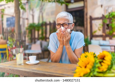 Woman with with allergy symptom blowing nose.  Rhinitis, cold, sickness, allergy concept. Pretty sick woman has runnning nose, rubs nose with handkerchief at cafe.