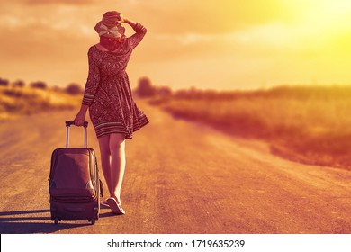 Woman alone in a dress and a summer hat traveling with luggage in a hot climate place during sunset. Hitchhiking concept