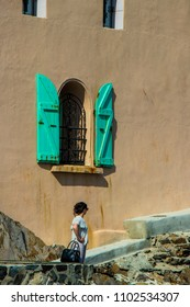 Woman alone at the foot of a Mediterranean house in Collioure, Eastern Pyrenees in southern France