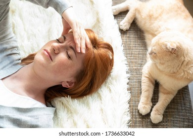 Woman alone, lying on a sofa alone in a room. Next to her cat. Depressed young woman at home. Stressed unemployed women. Depression, frustration and pain.