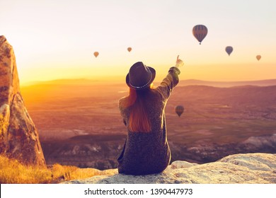 A woman alone unplugged sits on top of a mountain and admires the flight of hot air balloons in Cappadocia in Turkey. Digital detox and soul search