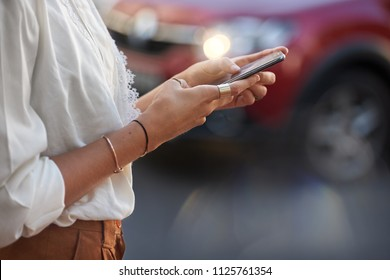 Woman alone using e-hailing taxi cab app on phonr for transport in foreign city