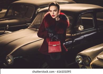 Woman among retro cars in garage