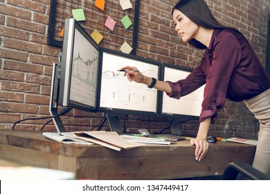 Woman analyzing data, graphs and reports,showing, pointing finger monitor. Indoor, studio shot. Business people concept, work in office