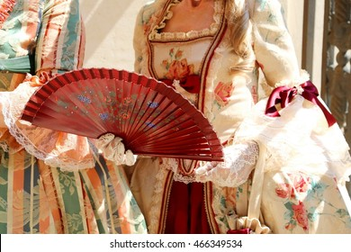 woman with an ancient ceremonial dress and the fan in her hand with white glove
