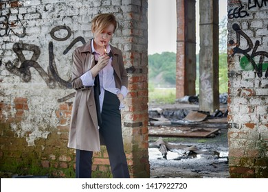 Woman of androgynous appearance and short blonde hair bob hairstyle in a coat, men's white shirt, tie and trousers, smoking a cigarette in an abandoned room with brick walls. Noir detective cosplay