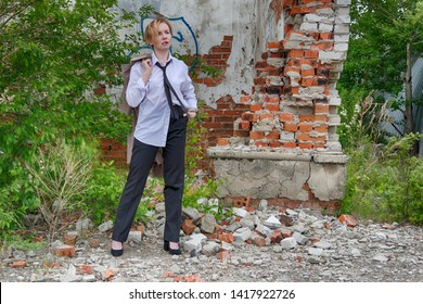 Woman of androgynous appearance and short blonde hair bob hairstyle with coat in hand, men's white shirt, tie and trousers, smoking a cigarette with an abandoned ruins on background. Noir detective.