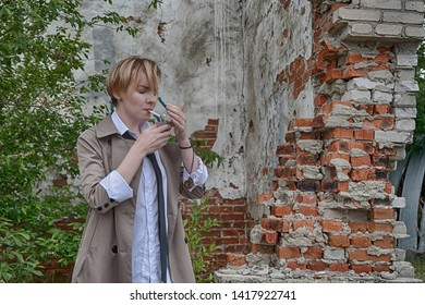 Woman of androgynous appearance and short blonde hair bob hairstyle in a coat, men's white shirt, tie and trousers, smoking a cigarette with an abandoned ruins on background. Noir detective or police
