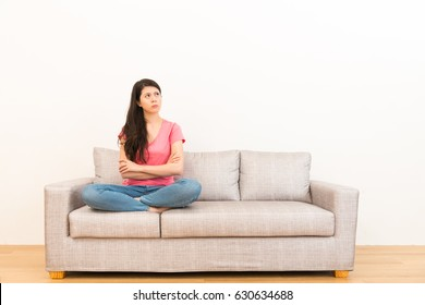 woman angrily unhappy thinking about family bad matters sitting on living room sofa in wood flooring with white background.