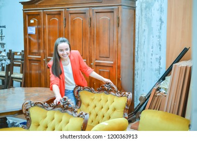 woman in antique shop is looking at old vintage furniture