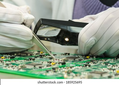 Woman in antistatic gloves holding pincette and magnifier repairing electronic components on PCB