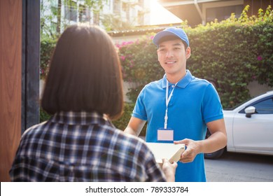 Woman appending receive sign signature after accepting a delivery of boxes from delivery man, sign and receive delivery concept