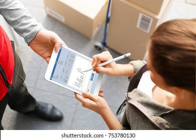 Woman appending signature after receiving parcel from courier outdoors