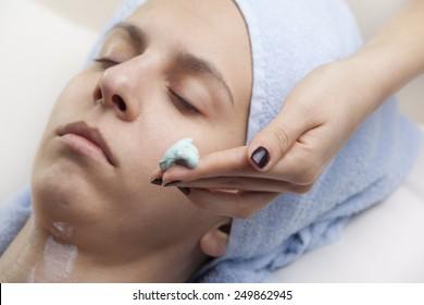 woman applaying facial mask to girl