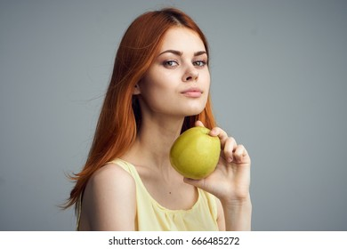 Woman with an apple on a gray background