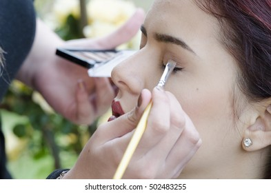 Woman applied eyeliner by makeup artist, outside the garden. Makeup artist apply eyeliner on the clients eyes