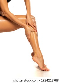 woman applies lotion on her beautiful legs on a white background