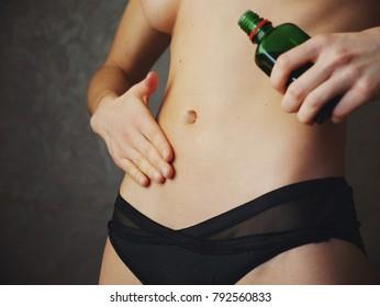 Woman apply body oil cream on abdomen