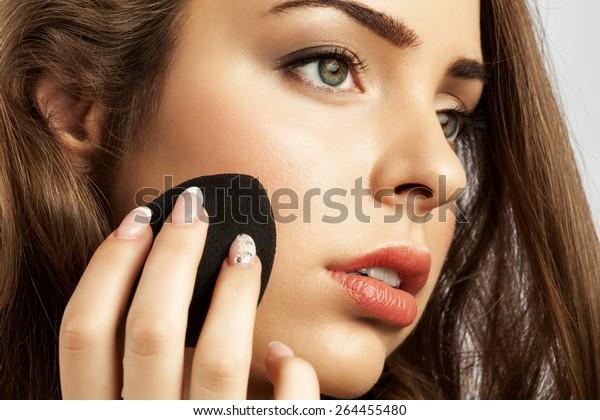 woman apply a sponge egg foundation