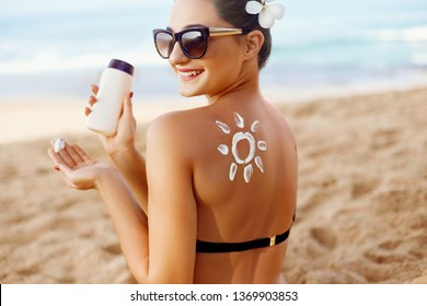 Woman apply Sun cream on tanned  back. Skin and Body Care. Sun protection. Portrait of Female in Bikini applying moisturizing sunscreen lotion and Sunblock. Girl Holding Suntan Lotion.