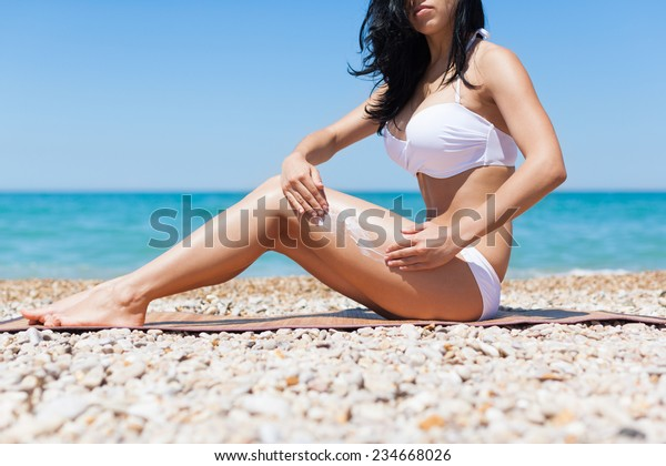 woman apply sunscreen protection lotion hand on hip long legs, young girl with tanned body, sitting on summer beach travel ocean vacation, female applying suntan cream skin care sun protect