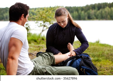 A woman applying an ankle bandage on a male camper